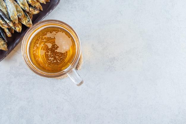 Gedroogde kleine gezouten sprot op een schotel naast bierglas, op de marmeren achtergrond.
