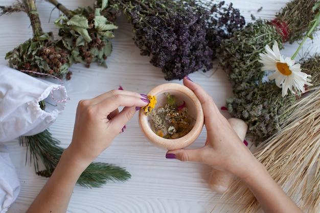 Gedroogde kruiden en bloemen in witte mortel op rustieke bord, zomerdecoratie, kruidengeneeskunde