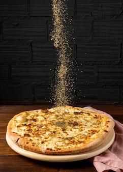 Gedroogde kruiden onder hoge hoek gestrooid over pizza