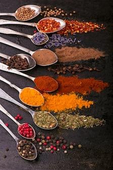 Gedroogde kruiden - peper, kurkuma, paprika, anijs, lavendel, adjika, koriander in oude lepels op een zwarte achtergrond
