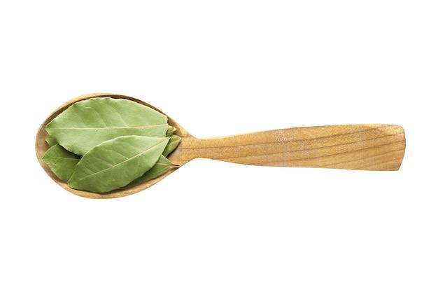Gedroogde laurierblaadjes om toe te voegen aan voedselkruiden in een houten lepel