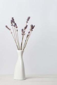 Gedroogde lavendelbloemen in witte vaas op houten oppervlak op lichte achtergrond. interieur bloemen compositie.