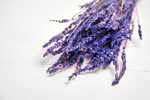 Gedroogde lavendelbloemen op houten tafel, bos van paarse lavendelplanten op witte achtergrond
