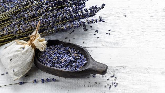 Gedroogde lavendelbos en textielzakje met gedroogde lavendelbloemen op een witte rustieke houten tafel.