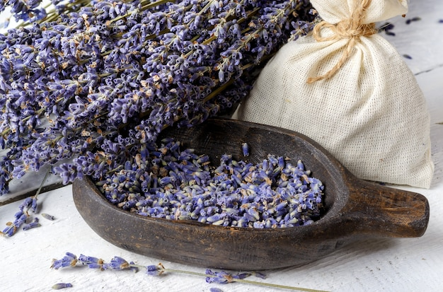 Gedroogde lavendelbos, lavendelbloemen in houten kom en zakje van textiel op een witte rustieke houten tafelclose-up.