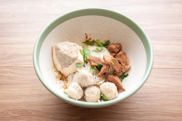 Gedroogde noedels met gekookt varkensvlees, varkensgehaktbal en tofu en varkensvlees in de kom