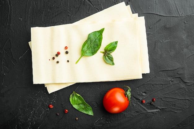Gedroogde ongekookte lasagne pastabladen, met kruiden en kruiden, op zwart
