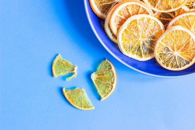 Gedroogde oranje fruitplakken op een blauwe keramische plaat, blauw papier fruit minimaal concept.