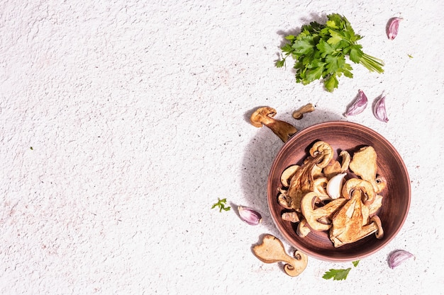 Gedroogde paddestoelen boletus edulis (penny bun, cep, porcini) op getextureerde gips achtergrond. ingrediënt voor vegetarisch (veganistisch) gezond voedsel. een trendy hard licht, donkere schaduw, bovenaanzicht