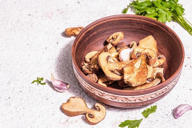 Gedroogde paddestoelen boletus edulis (penny bun, cep, porcini) op getextureerde gips achtergrond. ingrediënt voor vegetarisch (veganistisch) gezond voedsel. een trendy hard licht, donkere schaduw, close-up
