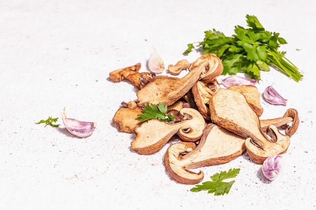 Gedroogde paddestoelen boletus edulis (penny bun, cep, porcini) op getextureerde gips achtergrond. ingrediënt voor vegetarisch (veganistisch) gezond voedsel. een trendy hard licht, donkere schaduw, kopieerruimte