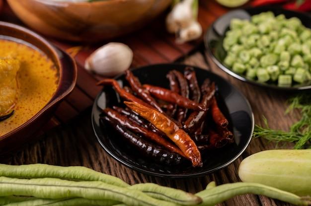 Gedroogde pepers gebakken in een zwarte plaat met linzen. komkommers en knoflook worden op de houten tafel geplaatst