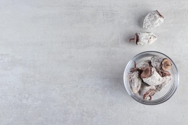 Gedroogde persimmonvruchten met suikerpoeder op steenachtergrond.