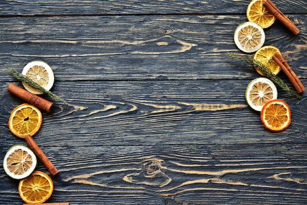 Gedroogde plakjes sinaasappel en limoen en kaneelstokjes op een donkere houten achtergrond. natuurlijk licht. bovenaanzicht.