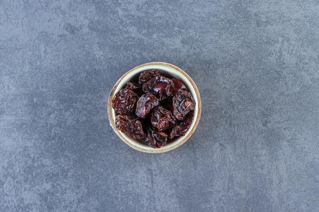 Gedroogde pruim in een kom op een bord op het marmeren oppervlak