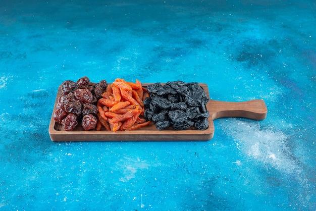 Gedroogde pruimen en abrikozen op een bord op het blauwe oppervlak