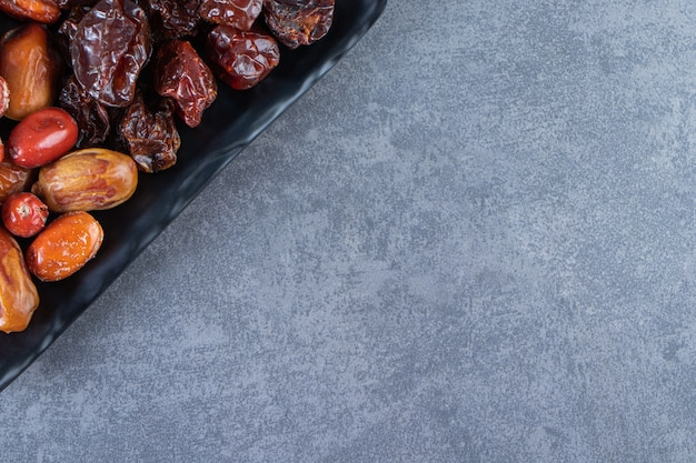 Gedroogde pruimen en oleaster op een bord, op de marmeren achtergrond.