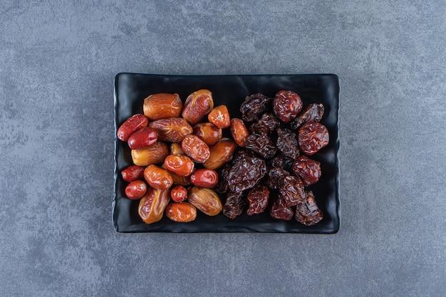 Gedroogde pruimen en oleaster op een bord, op het marmeren oppervlak