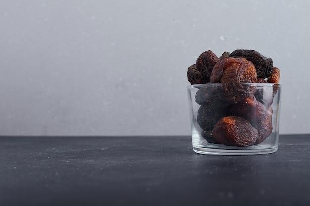 Gedroogde pruimen in een glazen beker op een grijze achtergrond.