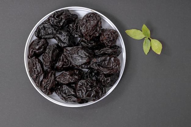 Gedroogde pruimen zonder pit geserveerd op grijs