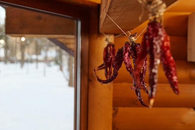 Gedroogde rode chili peper opknoping van een touw op een houten muur