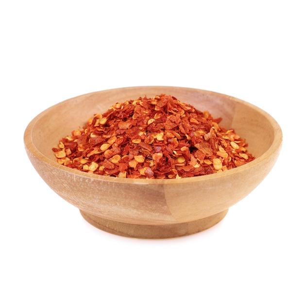 Gedroogde rode chili peper vlokken in houten kom isoleren op witte achtergrond
