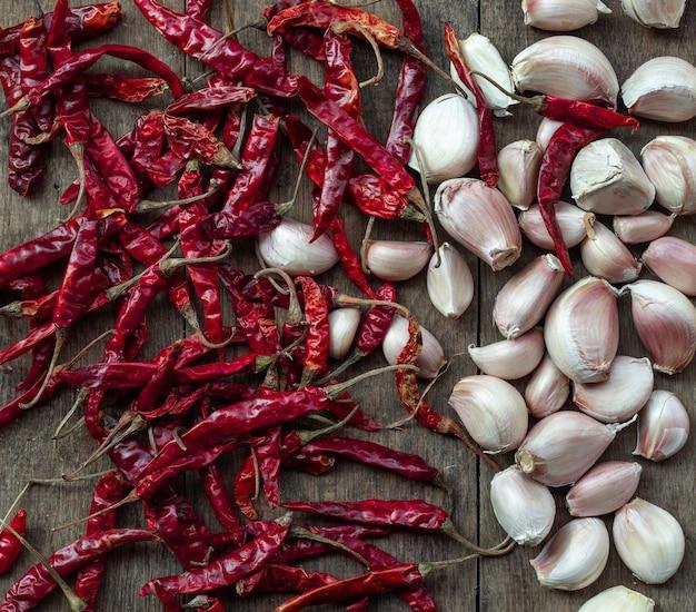 Gedroogde rode pepers en knoflook zijn plantaardige ingrediënten van kruiden op een bruine houtstructuurachtergrond