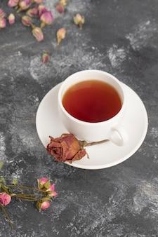 Gedroogde rosebuds met een kop hete thee op een stenen tafel.