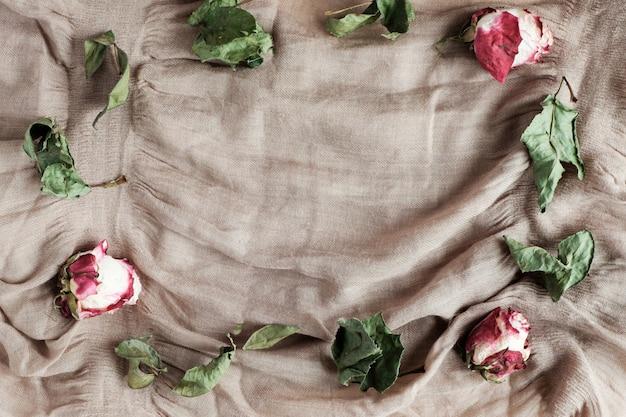 Gedroogde rozen en bladeren op beige stof achtergrond met kopie ruimte, bovenaanzicht