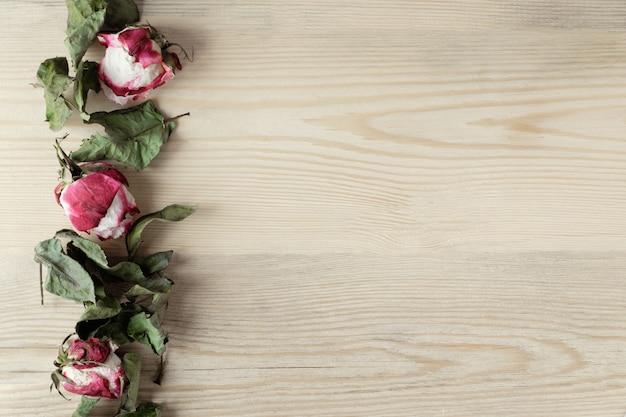 Gedroogde rozen en bladeren op houten achtergrond met kopie ruimte, bovenaanzicht