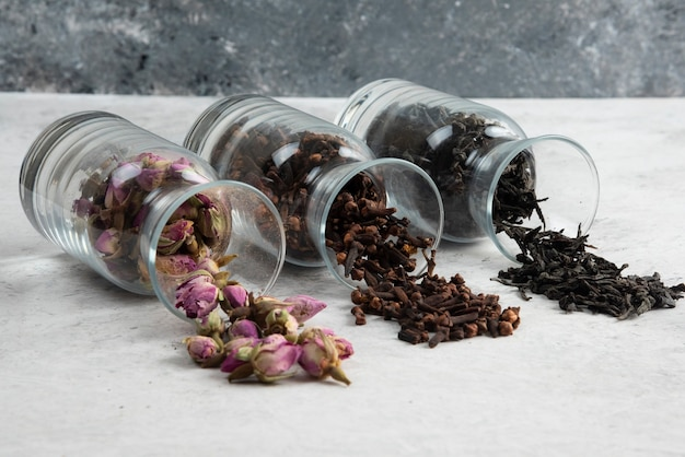 Gedroogde rozen met losse thee op grijs.