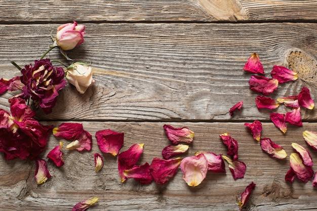 Gedroogde rozenblaadjes op houten tafel