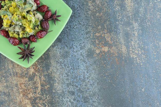 Gedroogde rozenbottels en bloemen op groene plaat.