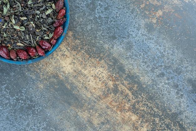Gedroogde rozenbottels en theeblaadjes op blauw bord.