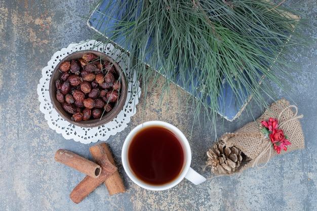 Gedroogde rozenbottels, kopje thee en kaneel op marmeren oppervlak. hoge kwaliteit foto