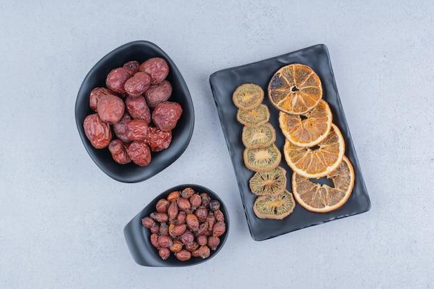 Gedroogde rozenbottels, zilverbes, kiwi en sinaasappels op marmeren oppervlak.