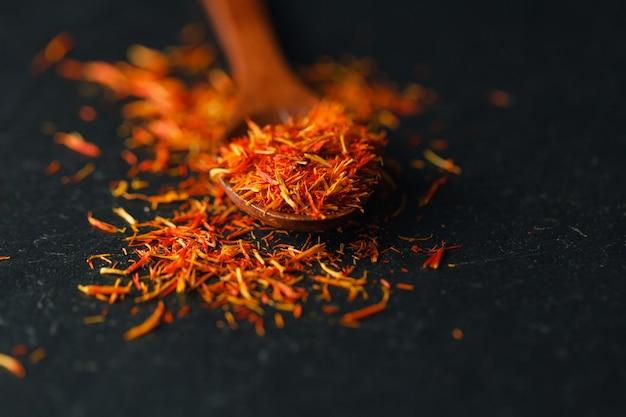 Gedroogde saffraan kruid op zwarte tafel. ruwe organische saffraanpoeder saffraan zijn verspreid op de tafel. rood saffraankruid in een houten lepel op zwarte lijst