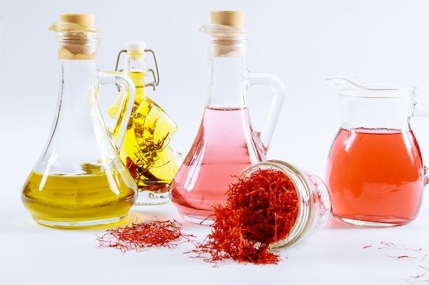 Gedroogde saffraandraden in een glazen fles en olie-extract op een witte achtergrond.