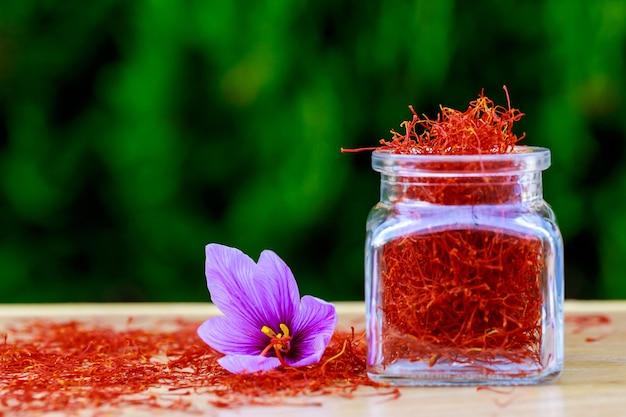Gedroogde saffraankruiden in een fles en saffraanbloem op een houten tafel.