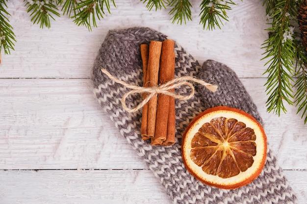 Gedroogde sinaasappel en kaneelstokjes op handschoen. houten kerst concept