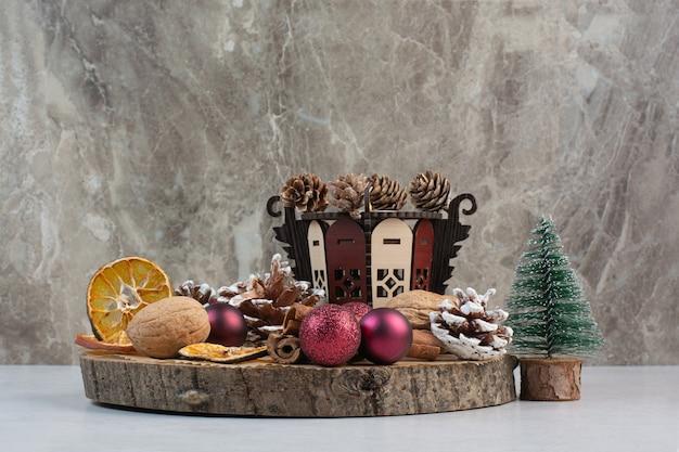 Gedroogde sinaasappel met dennenappels en kerstballen op houten plaat. hoge kwaliteit foto