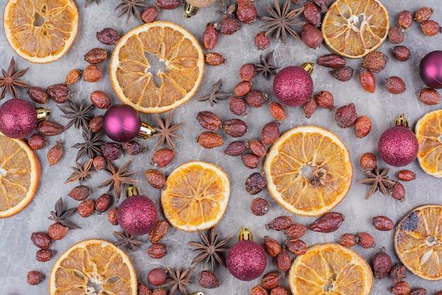 Gedroogde sinaasappel met kerstballen en rozenbottels op stenen oppervlak.