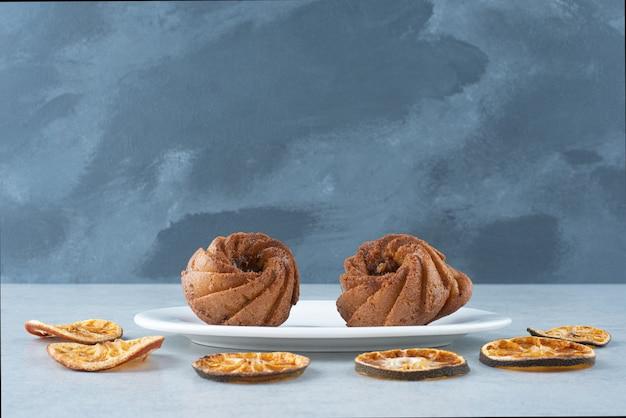Gedroogde sinaasappel met twee heerlijke cupcakes op witte achtergrond