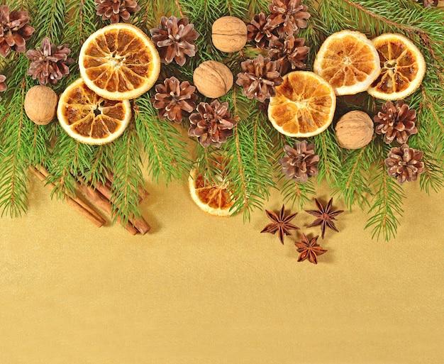 Gedroogde sinaasappelen en kegels en sprusetak op een gouden achtergrond