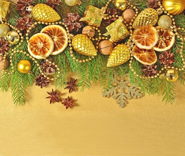 Gedroogde sinaasappelen en kegels kerstversiering en spruse tak op een gouden achtergrond