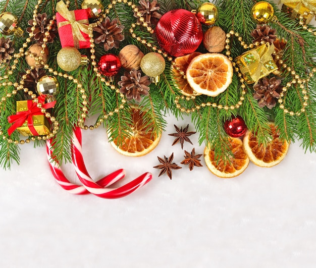 Gedroogde sinaasappelen en kegels kerstversiering en spruse tak op een witte achtergrond