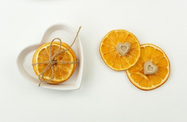 Gedroogde sinaasappels met bruine suiker in de vorm van het hart liggen op een wit bord