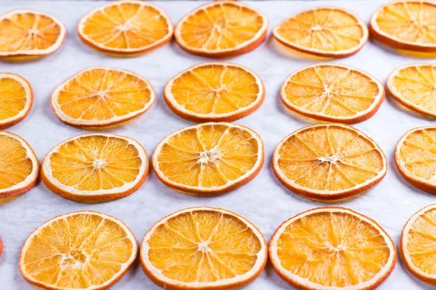 Gedroogde sinaasappels. proces van voorbereiding van oranje gekonfijte vruchten voor nieuwjaar en kerstfeest