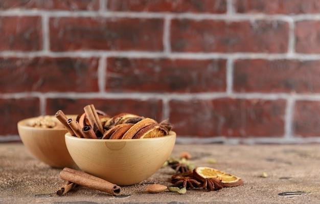 Gedroogde sinaasappelschijfjes, kaneelstokjes, anijssterren, kardemomzaadjes in houten kommen