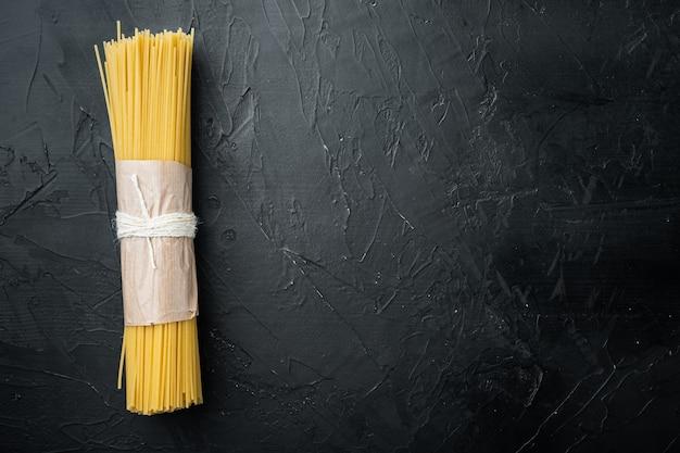Gedroogde spaghetti pasta, op zwart, bovenaanzicht plat lag